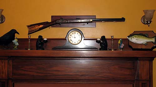 Photo of a gun mounted above fireplace