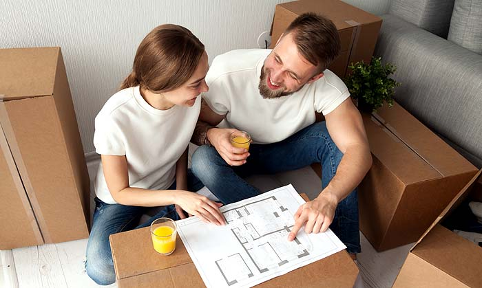 Photo of a couple moving into a new home with floorplan
