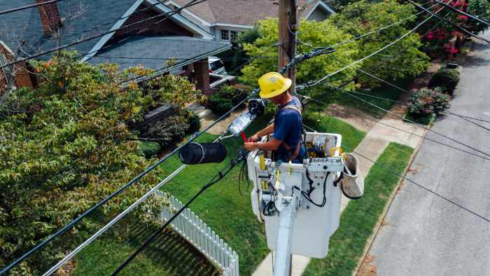 Photo of an electrical worker at the power lines