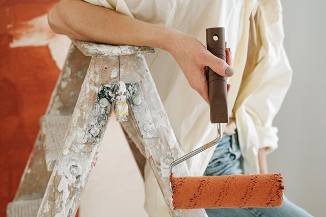 Photo of a woman painter holding a paint roller